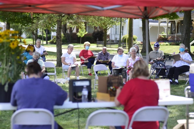More than a dozen senior citizens play bingo outside last summer at the Crawford County Council on Aging. The council's building at 200 S. Spring St. will reopen to the public on July 6.