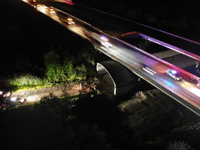 Car headlights illuminate the scene where a Fairfield, Ohio man died Tuesday, Aug. 18 after falling off a bridge on I-65 in Clinton County, Indiana. Police said the man was trying to assist after a semi-truck overturned and caught fire.