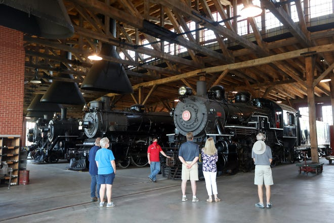 A tour guide talks about a steam locomotive at the Age of Steam Roundhouse in Sugarcreek. The roundhouse houses the steam engine collection of the late Jerry Joe Jacobson, who founded the Ohio Central Railroad.