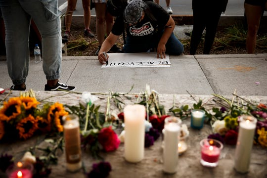 Candles and flowers sit on the steps of the old City Hall building as protesters march with members of the Black Liberation Movement calling for justice for Black children on Thursday, Aug. 20, 2020 in Des Moines.