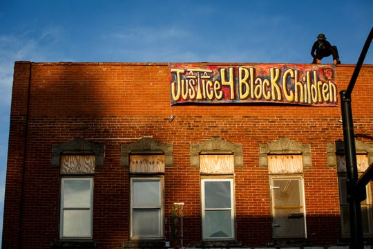 Protestors marched to the old City Hall building in the cities River Bend neighborhood where they hung signs and held a vigil calling for justice for Black children on Thursday, Aug. 20, 2020 in Des Moines.