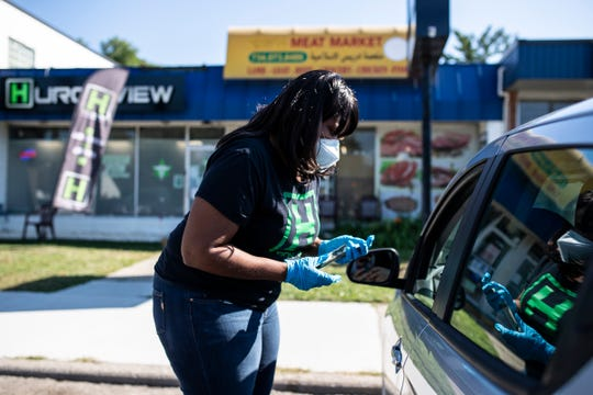 Teesha Montague delivers an order for curbside pickup outside of Huron View Dispensary in Ann Arbor on August 20, 2020.