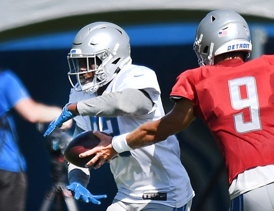 Detroit Lions' Kerryon Johnson takes the handoff from Matthew Stafford during NFL football training camp practice in Allen Park, Mich., Friday, Aug. 21, 2020.