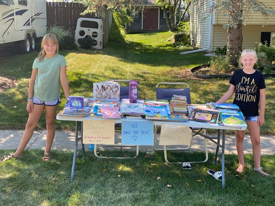 Nola Sprester (right) and her friend Kendra Lauersdorf stand by the table in Nola's yard that holds old books that people could pick up and also donate money to the Oconomowoc Police Department.