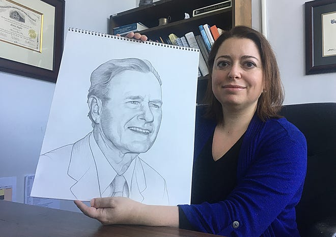 Elana Hagler, an assistant professor of art at Alabama State University, holds her drawing of President George H.W. Bush, which is being used in an upcoming $1 presidential collectors coin from the U.S. Mint.