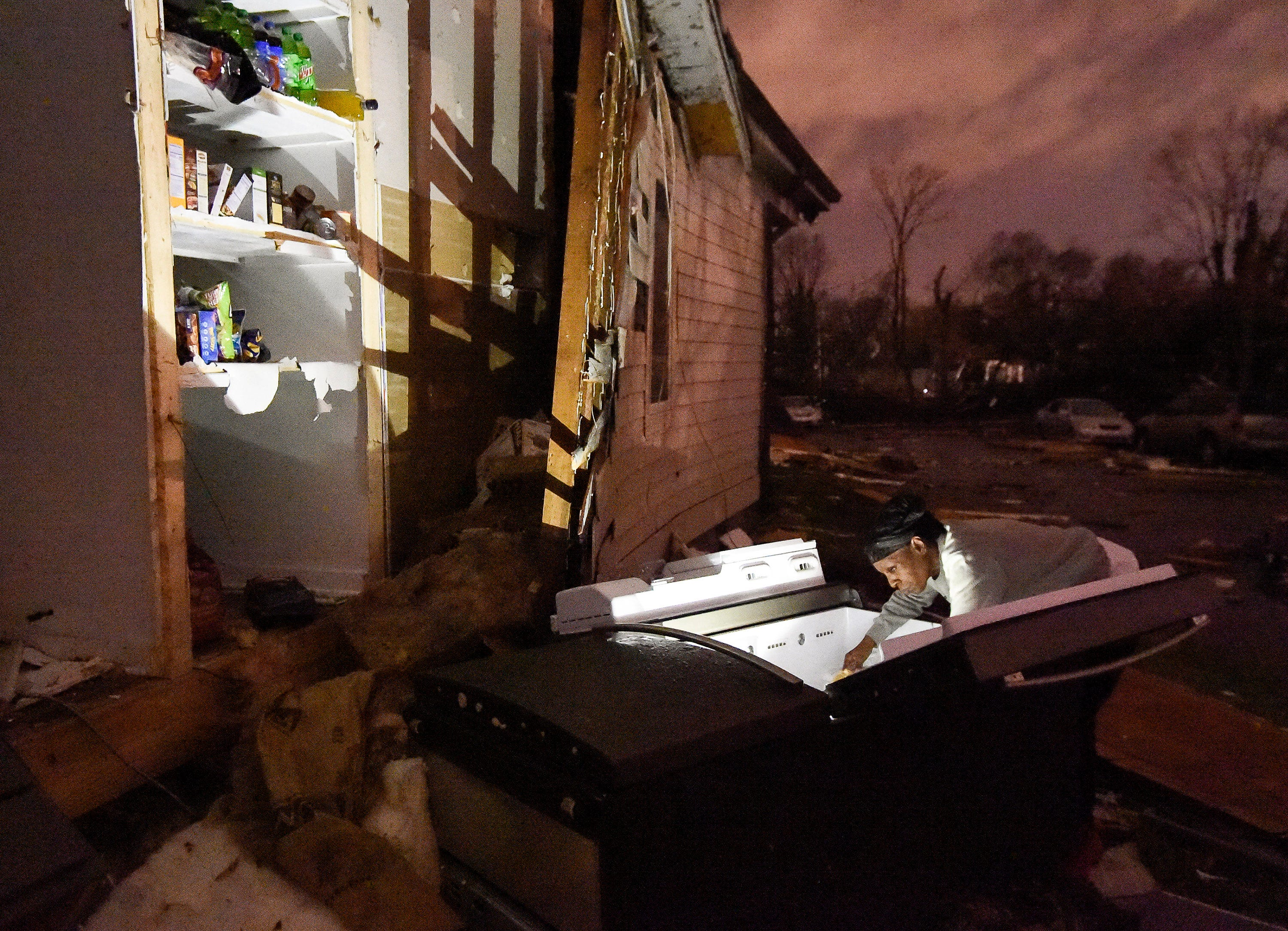 A woman looks through her refrigerator after it was ripped out of her home at Underwood St. and 16th Ave. N.