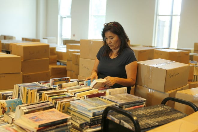 Sharon Blue Eyes, the technical services director at the Farmington Public Library, sorts items included in the annual book sale at the library in this 2017 file photo. This year's sale has been called off.