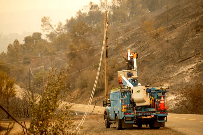 As the LNU Lightning Complex fires burn nearby, a PG&E worker clears a power line blocking a roadway in unincorporated Napa County, Calif., on Thursday, Aug. 20, 2020. Fire crews across the region scrambled to contain dozens of wildfires sparked by lightning strikes. (AP Photo/Noah Berger)