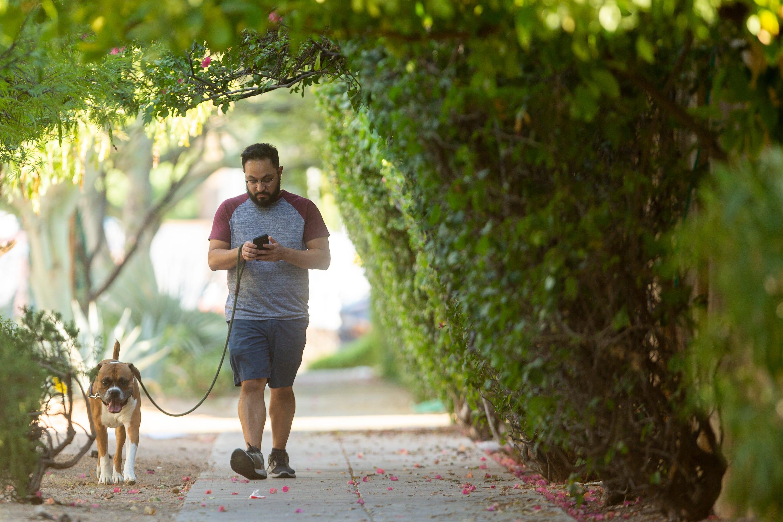 Ramon Rojas walks Dutch the dog down Third Avenue in Phoenix on July 15, 2020.