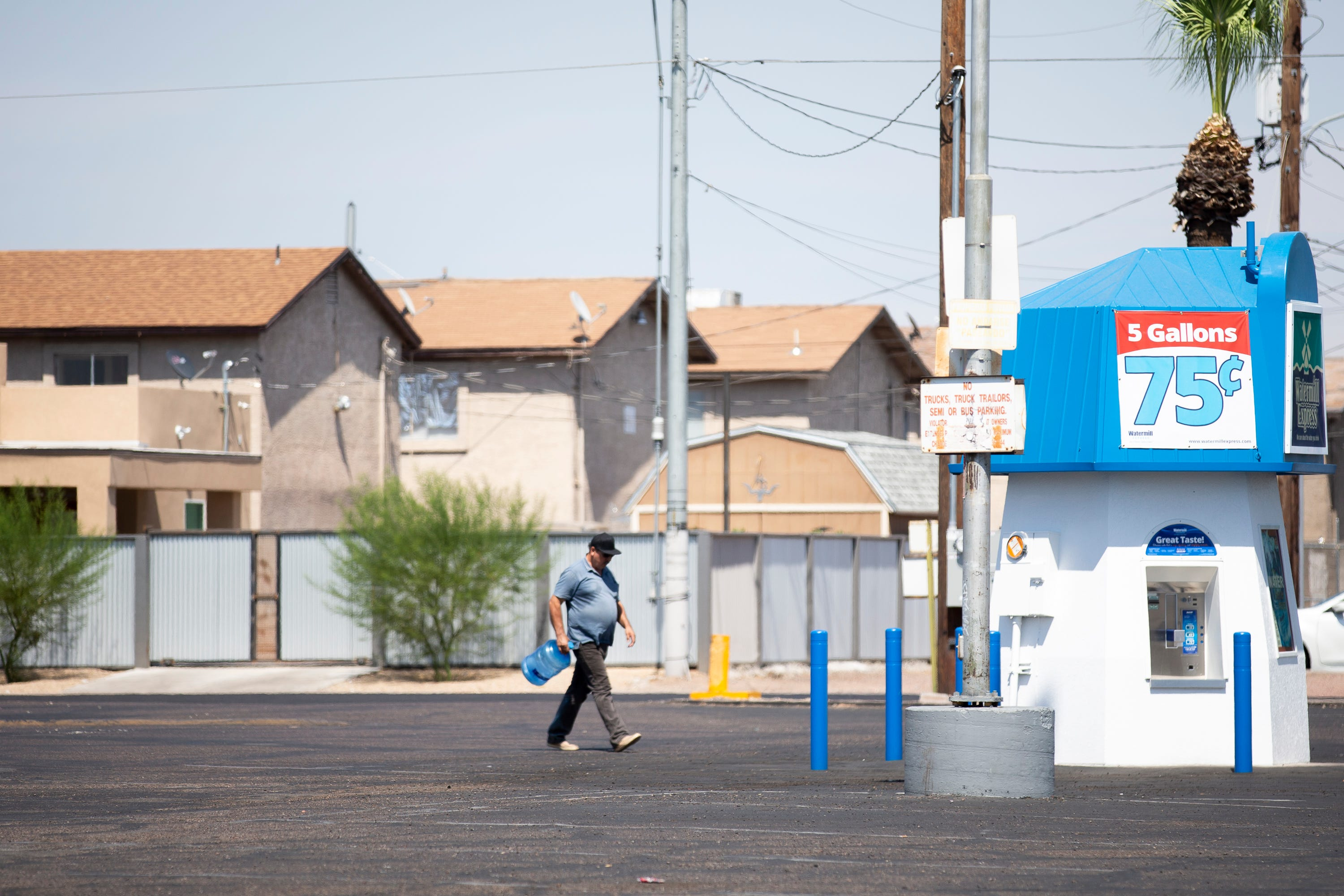 A man carries an empty jug to be filled at a water station at the corner of Van Buren Street and 33rd Avenue in Phoenix on July 15, 2020.