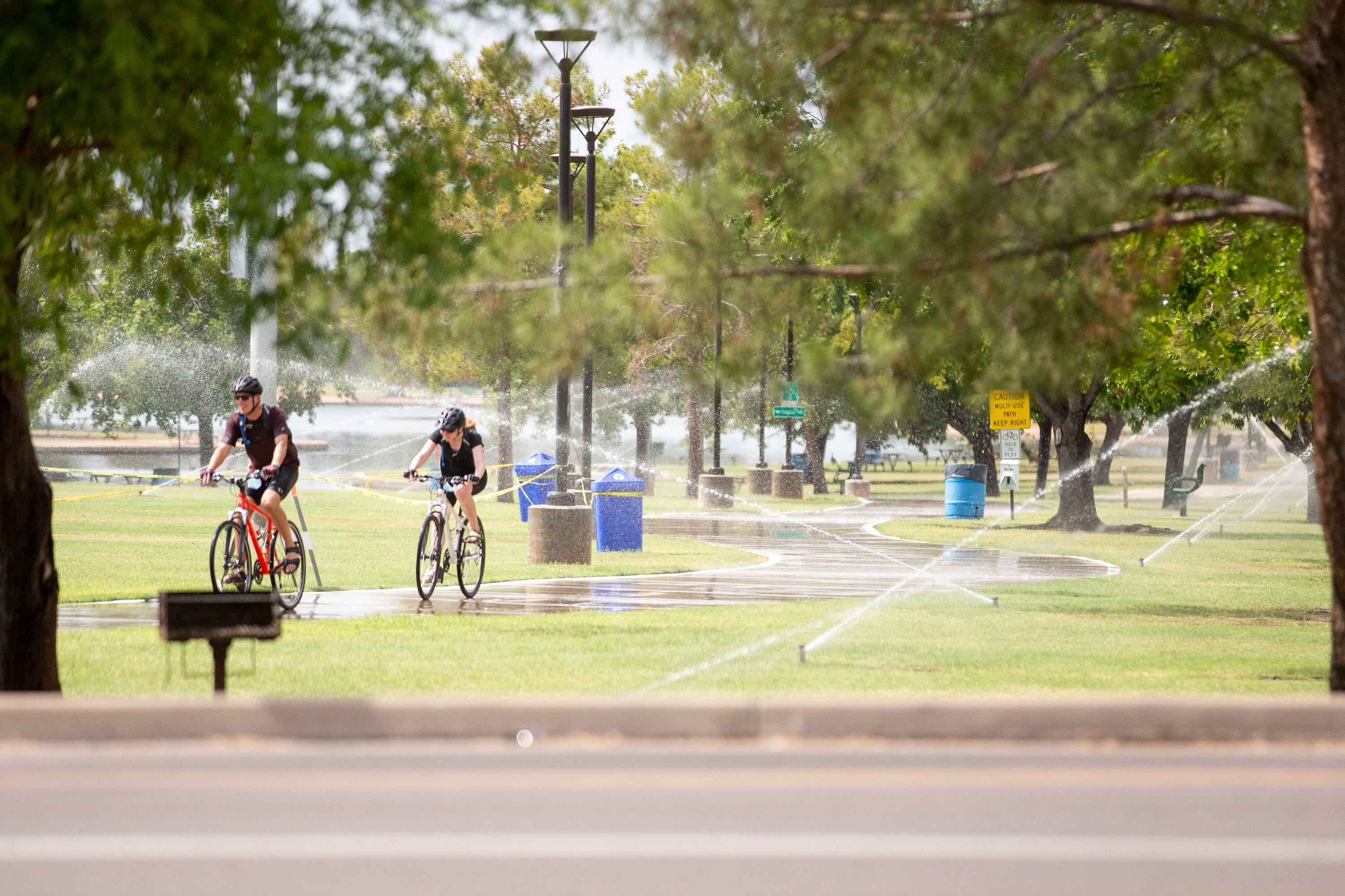 Bicyclists enjoy a ride through sprinklers at Chaparral Park in Scottsdale on July 13, 2020. The temperature for the day was expected to reach a high of 112 degrees Fahrenheit.