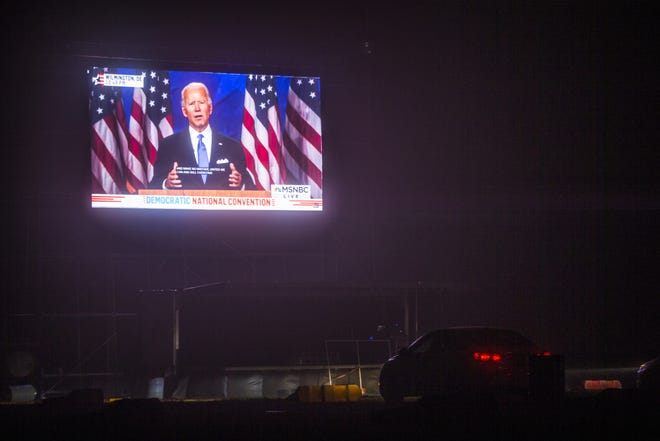 Democratic presidential candidate Joe Biden speaks on a big screen during an Arizona Democratic Party drive-in night in Mesa on Aug. 20, 2020. Delegates could watch the acceptance speech of party nominee Biden.