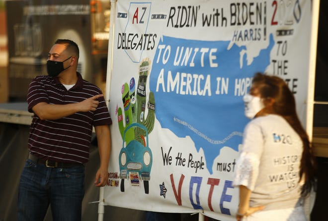 "Arizona delegate Martin Quezada and Cinthia Estela pose with a ""Ridin' with Biden"" poster during an Arizona Democratic Party drive-in night to watch the acceptance speech of their party's nominee, Joe Biden, in Mesa, Ariz. on August 20, 2020."