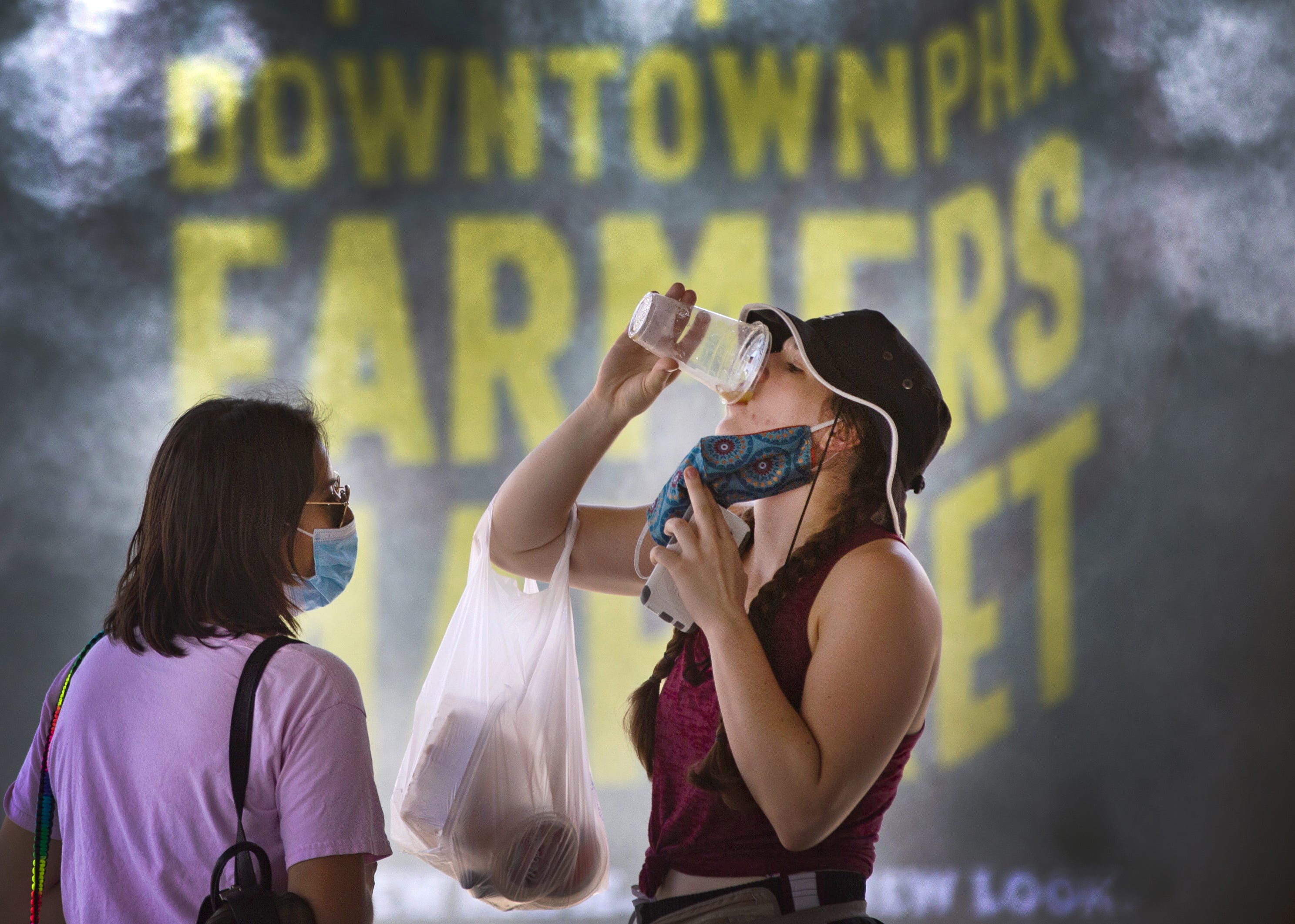 Samantha Godoy, left, and Katie Kelly, of Phoenix, keep cool under misters at the Downtown Farmers Market on July 25, 2020.