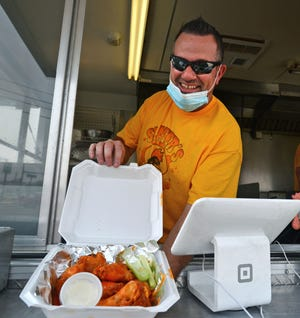 Jay Slater shows off his wings from inside the Slater's Ding-a-Wing food truck on August 21, 2020. Slater's offers wet and dry wings, chicken tenders, and house specials and house fries.