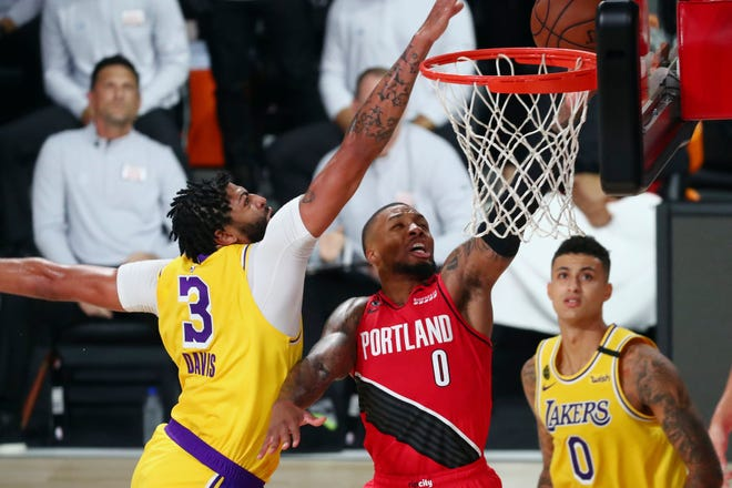 Los Angeles Lakers forward Anthony Davis (3) blocks a shot by Portland Trail Blazers guard Damian Lillard (0) as Lakers forward Kyle Kuzma (0) looks on during the first half of Game 2 of an NBA basketball first-round playoff series, Thursday, Aug. 20, 2020, in Lake Buena Vista, Fla.