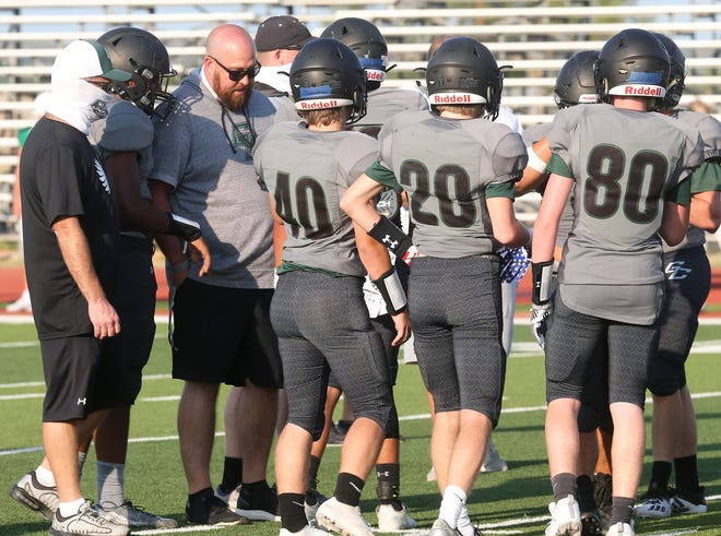 Grape Creek head football coach Tanner Thiel goes over the game plan with the Eagles during a three-team scrimmage with Wall and Monahans at Grape Creek High School on Thursday, Aug. 20, 2020.