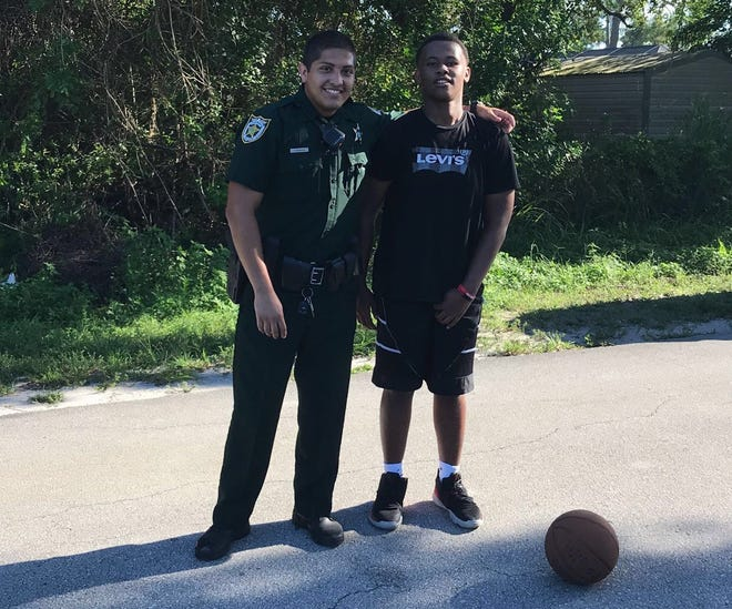 "Deputy Daniel Herrera of the St. Lucie County Sheriff's Office and Antwan ""A.J."" Jones, 15, played a quick game of pick-up basketball on August 7, 2020. A video that was captured by A.J.'s mother, Tameshia Martin, was posted on Facebook, went viral and was shared on FOX News."