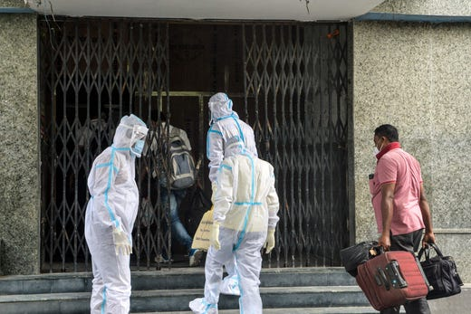 Health workers wearing Personal Protective Equipment (PPE) suits guide asymptomatic COVID-19 patients to the entrance of the Siliguri Indoor Stadium, temporarily converted into a COVID-19 coronavirus safe home care centre, in Siliguri, India on August 21, 2020.
