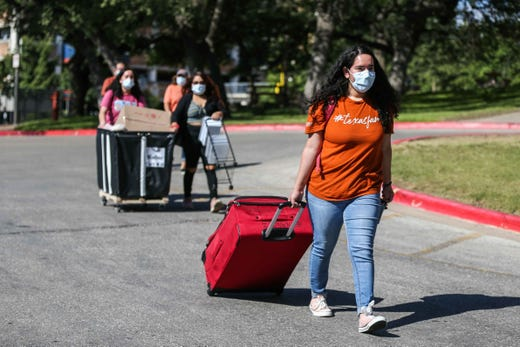Alyssa Hernandez carries a suitcase as her family help her to move in to the Jester West Dormitory at the University of Texas in Austin on Thursday, August 20, 2020.