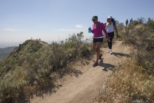 People hike along a ridge where vegetation is quickly drying out in Griffith Park on March 29, 2015, in Los Angeles.