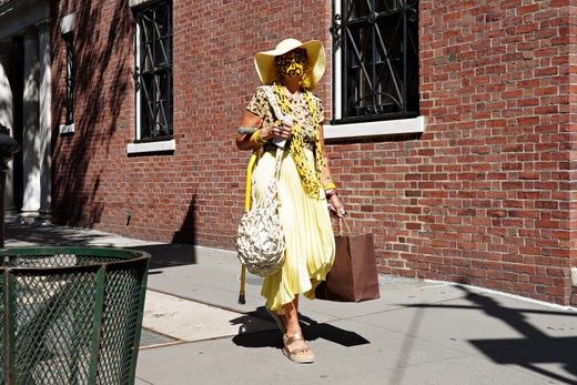 NEW YORK, NEW YORK - AUGUST 20: A woman wearing a yellow outfit with matching protective mask walks down the sidewalk as the city continues Phase 4 of re-opening following restrictions imposed to slow the spread of coronavirus on August 20, 2020 in New York City. The fourth phase allows outdoor arts and entertainment, sporting events without fans and media production. (Photo by Cindy Ord/Getty Images) ORG XMIT: 775526444 ORIG FILE ID: 1267433271