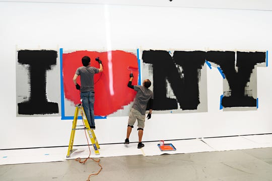 Painters install an oversized presentation of the iconic I Love NY logo inside the Museum of Modern Art ahead of its Aug. 27 reopening. The fourth phase of the state's reopening plan allows outdoor arts and entertainment, sporting events without fans and media production.