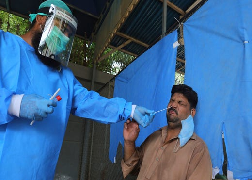 A man reacts while having a nasal swab sample taken at a testing and screening facility for the coronavirus, in a hospital in Karachi, Pakistan, Friday, Aug. 21, 2020.