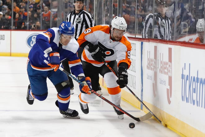 Flyers defenseman Ivan Provorov tries to keep the puck away from the Islanders' Casey Cizikas during a February game.
