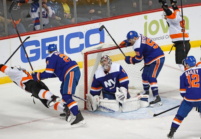 Islanders defenseman Scott Mayfield, 24, sends center Sean Couturier flying as Couturier celebrates a Flyers goal that Islanders goalie Semyon Varlamov laments during a February game. [Associated Press]