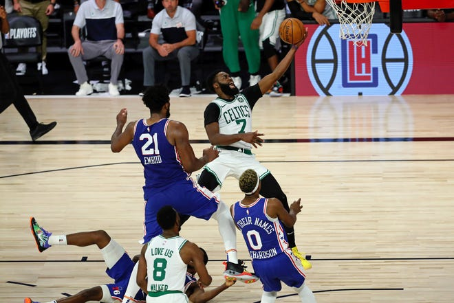 Celtics guard Jaylen Brown converts a three-point play to put Boston ahead for good with 1:37 remaining as the Sixers' Joel Embiid arrives too late.