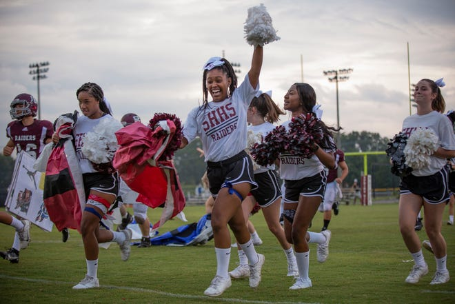 Spring Hill cheerleader Yaniyah Hardison rushes the field will her fellow squad members before the start of the first football game of the season in Spring Hill, Tenn., on Friday, Aug. 21, 2020.