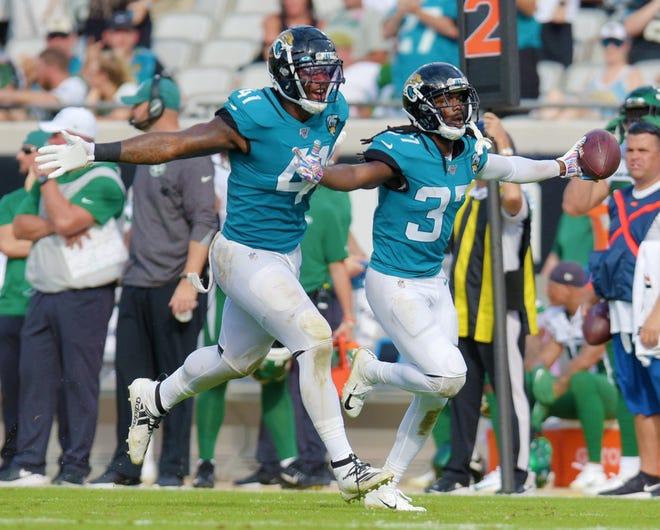 Jaguars defensive end Josh Allen (41) runs down the field with Tre Herndon (37) after a 2019 interception.