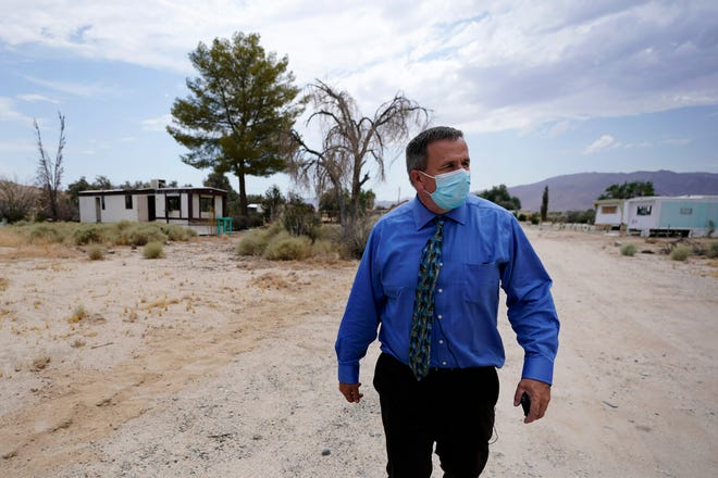 Tom Baumgarten, superintendent of the Morongo County School District, walks down a dirt road near the district offices in Twentynine Palms, Calif.  Baumgarten resigned on Nov. 10, 2020.