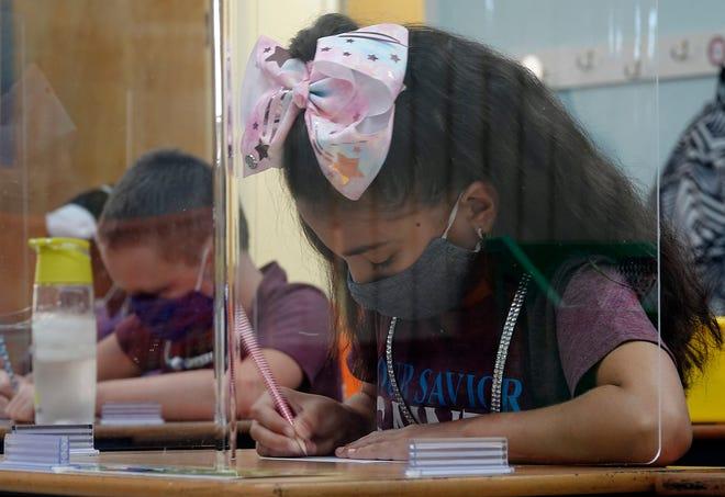 Third-grader Gabriela Natale studies behind plexiglass at her desk at Our Savior Lutheran Church and School in Plantation on Wednesday. Polk County's public schools reopen to students on Monday. [JOE CAVARETTA/SOUTH FLORIDA SUN-SENTINEL]