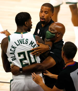 Milwaukee's Marvin Williams is held back after a fight with Orlando's James Ennis III during Game 3 on Saturday in Lake Buena Vista.