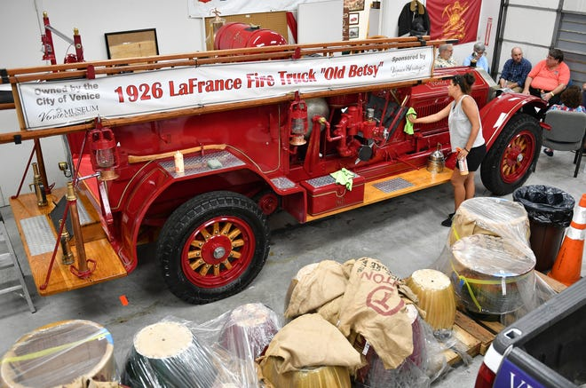 "Tara Ford of Apple Auto Detailing applies polish to the 1926 LaFrance fire truck ""Old Betsy"" before its 2019 appearance at the Sun Fiesta. Venice Heritage Inc. wants to build a permanent display building for the 94-year-old vehicle on the island of Venice."