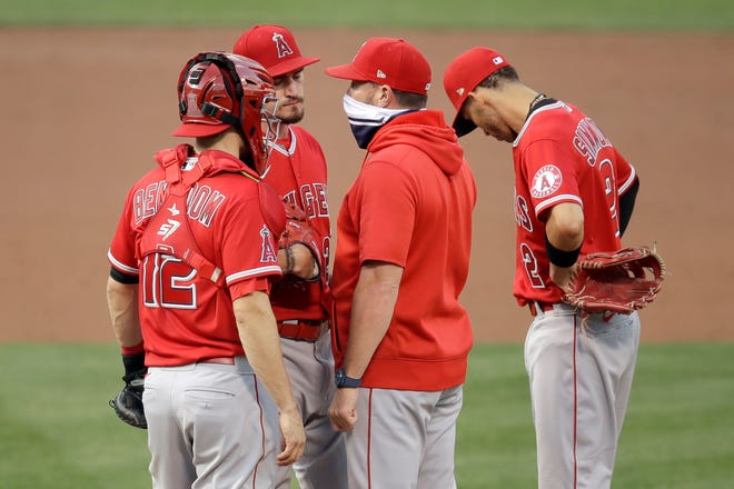 Los Angeles Angels pitcher Andrew Heaney, second from left, speaks with pitching coach Mickey Callaway, second from right, in the first inning of a baseball game against the Oakland Athletics Friday, Aug. 21, 2020, in Oakland, Calif.