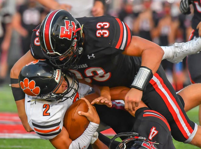 Lawrenceburg quarterback Garrett Yoon is tackled by East Central's Kole Viel in the Aug. 21, 2020, season opener with East Central.