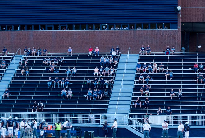 Fans gather in the stands as they distance themselves from other families during the Reitz Panthers  vs Harrison Warriors game at the Reitz Bowl in Evansville, Ind., Friday evening Aug. 21, 2020.