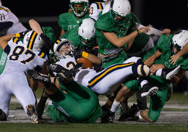 Castle's Peyton Guerzini (29) is brought down by the swarming North defense in the Knights' 14-7 loss on Aug. 21.