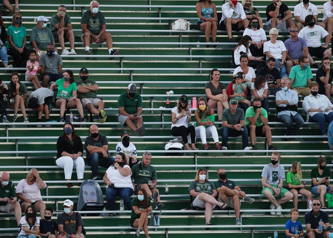 A high school football game in Indiana shows a mostly masked audience on Friday, Aug. 21, 2020. The North Carolina High School Athletic Association has put football on hold until February, and on Tuesday set a state championship date of May 8, 2021.