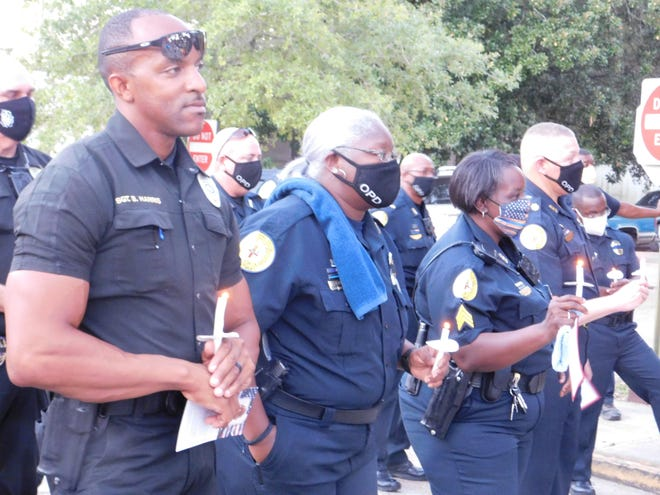Opelousas police officers gather with lighted candles as a prayer is read during a memorial service for fellow officer Gary Lazard, who died last week.