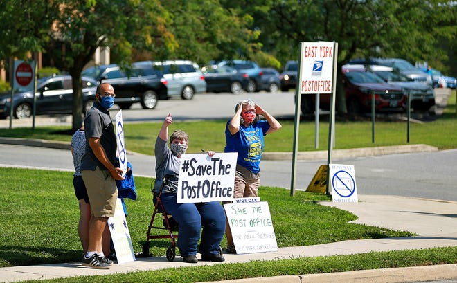 """Marta Peck, of Indivisible York, center, gives a thumbs-up to passersby as they honk for more than two dozen protesters gathered for """"Save the Post Office Saturday"""" at the East York Post Office in Springettsbury Township, Saturday, Aug. 22, 2020. Dawn J. Sagert photo"""