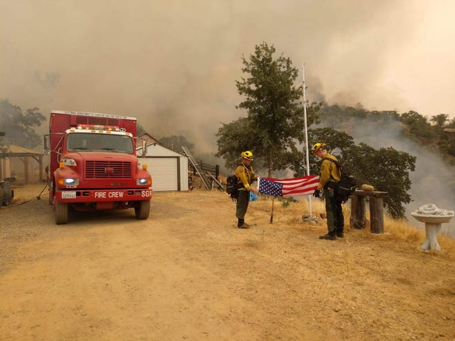 In a photo tweeted Friday, a firefighter hand crew from the Cal Fire Shasta-Trinity Unit saves an American flag while protecting buildings and conducting backfires on the Canyon Zone of the SCU Lightning Complex. The SCU Lightning Complex started Aug. 16, 2020, with 20 separate fires in Santa Clara, Alameda, Contra Costa, San Joaquin and Stanislaus counties, and have since merged into three major blazes.