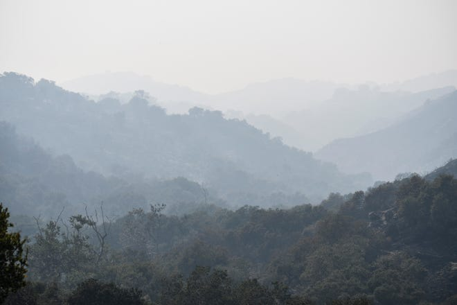 The hills behind Black Mountain Road were covered with smoke from multiple fires Friday. Aug. 21, 2020.