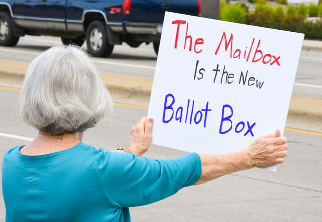 Joan Vincent holds a sign up at a rally for the U.S. Postal Service Saturday, Aug. 22, 2020, in Waite Park.