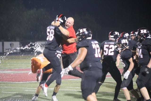 Hurricane head coach Skyler Miller embraces Jake Barlow (58) after Hurricane's 15-14 win over Murray on Aug. 21, 2020.