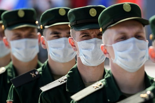 Russian servicemen wearing a face mask to prevent the spread of the COVID-19 pandemic, prepare to roll out a huge Russian national flag during a celebration ceremony of the National Flag Day at Poklonnaya Hill in Moscow on August 22, 2020.