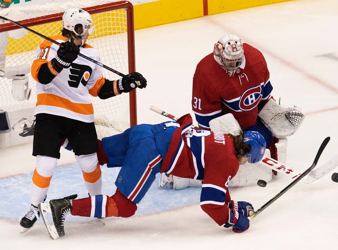 The Flyers' Travis Konecny levels the Canadiens' Ben Chiarot in front of Montreal goalie Carey Price.